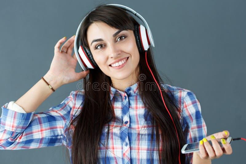 Beaux écouteurs de port de sourire d'une chevelure foncés de femme photographie stock