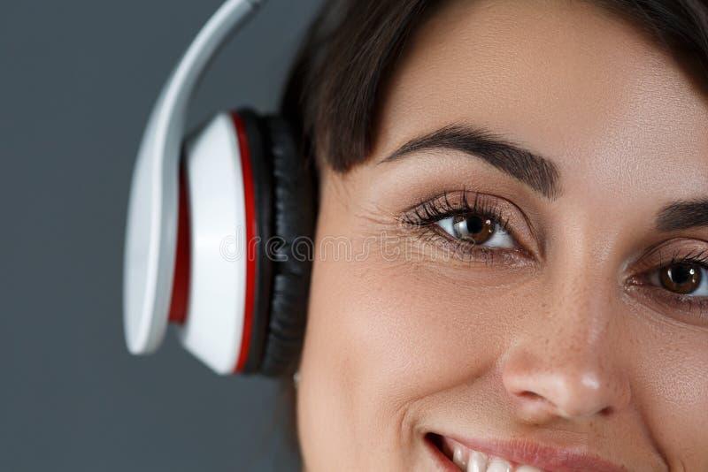 Beaux écouteurs de port de sourire d'une chevelure foncés de femme photo libre de droits