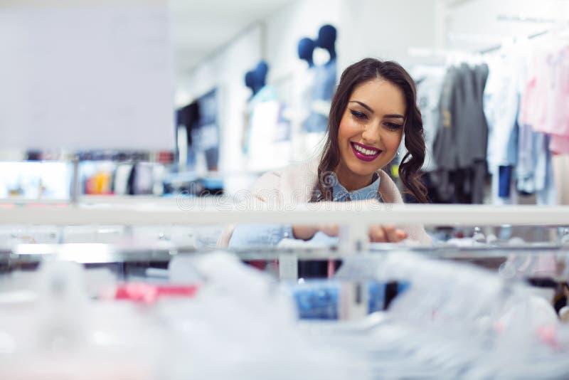 Beaux achats de jeune femme dans un magasin image stock