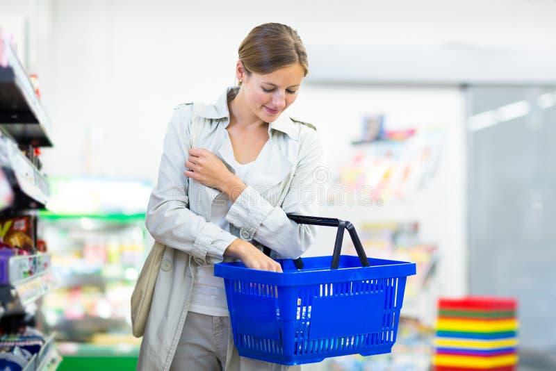 Beaux achats de jeune femme dans une épicerie/supermarché photographie stock libre de droits