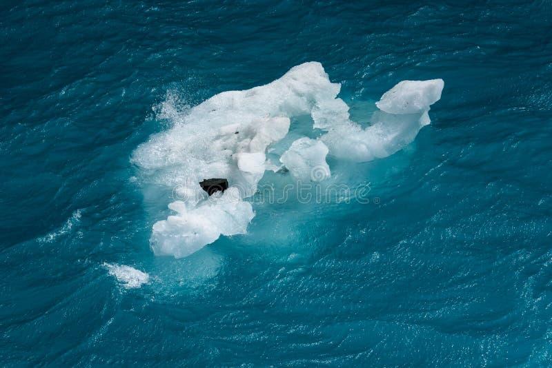Beaux aigues-marine et bleus d'océan avec un petit iceberg de flottement portant une roche, comme fond de nature images stock