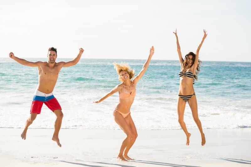 Beaux amis enthousiastes sautant sur la plage photos stock