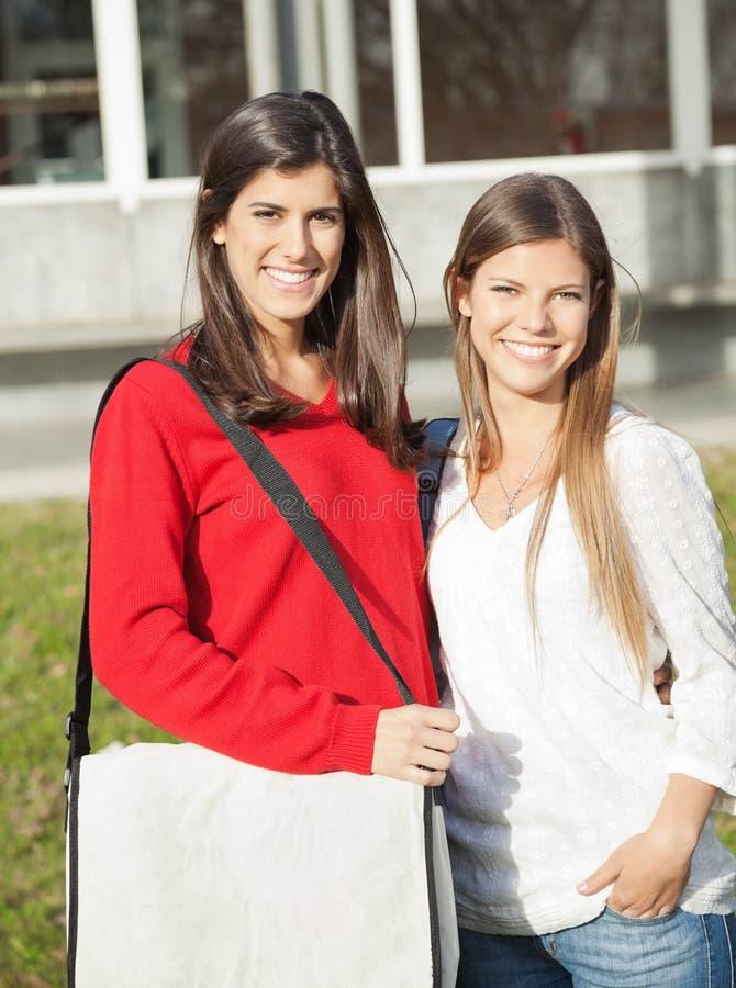 Beaux amis souriant ensemble sur l'université photo libre de droits
