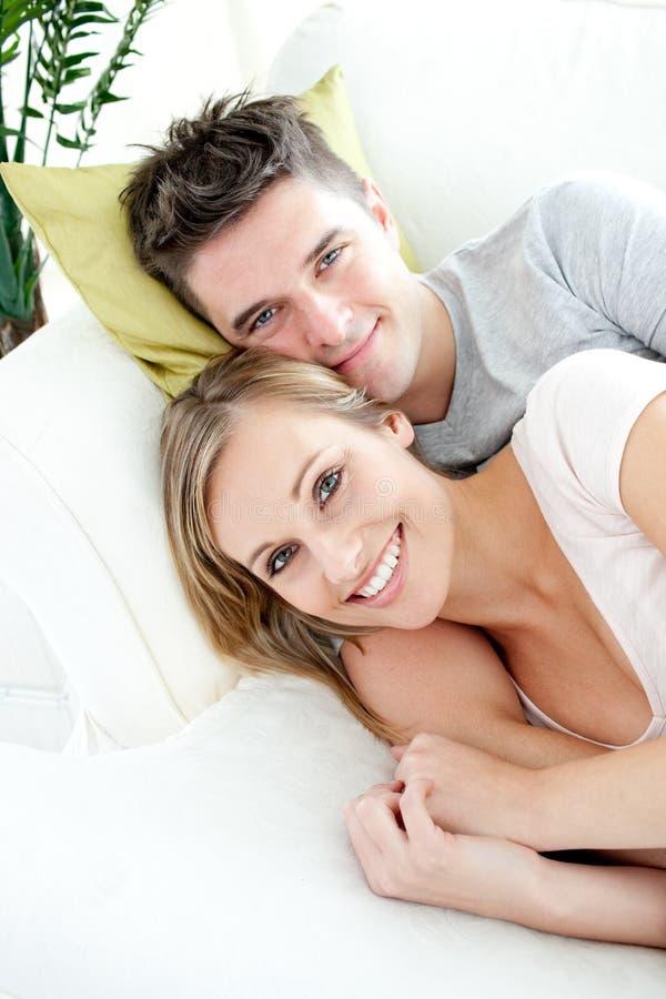 Beaux amoureux ayant l'amusement ensemble sur un sofa images stock