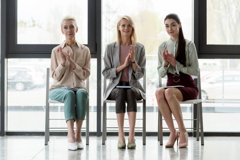 beaux applaudissements de trois femmes d'affaires photographie stock libre de droits