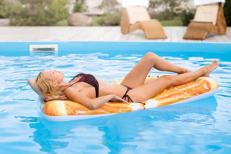 Beaux bains de jeune femme dans la piscine sur le jouet gonflable sous forme de morceau de fruit photographie stock