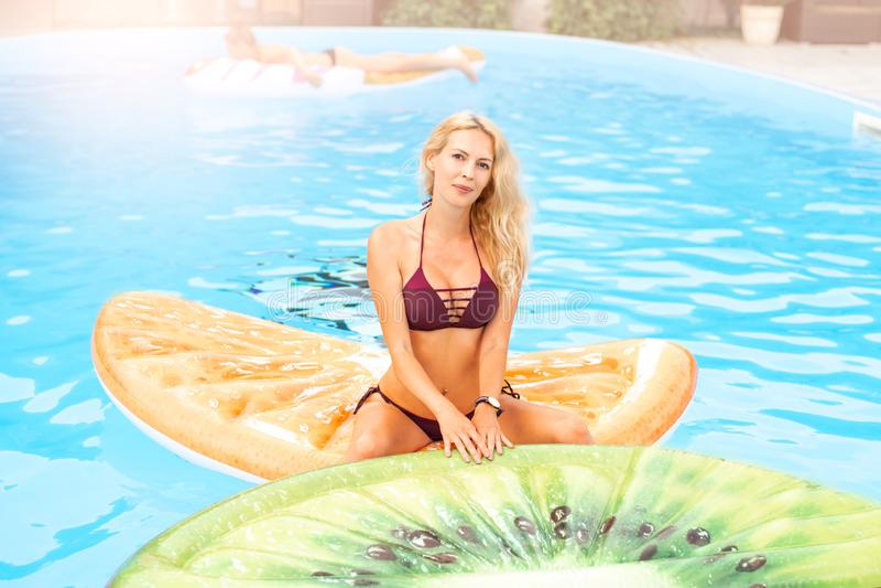 Beaux bains de jeune femme dans la piscine sur le jouet gonflable sous forme de morceau de fruit photo stock