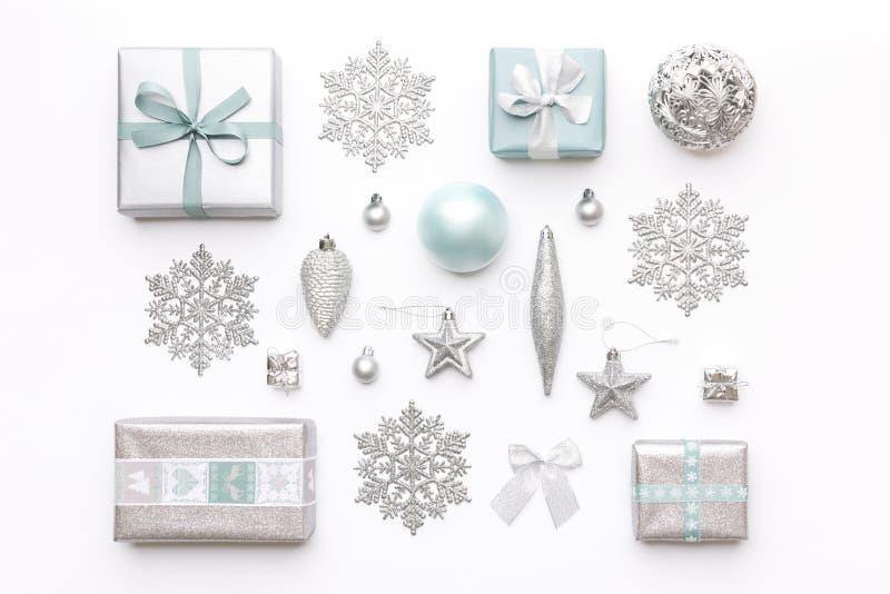Beaux cadeaux de Noël et flocons de neige et ornements argentés d'isolement sur le fond blanc Composition de Noël photos stock