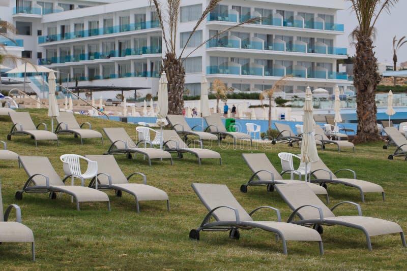 Beaux canapés du soleil sur la pelouse près de l'hôtel photos libres de droits
