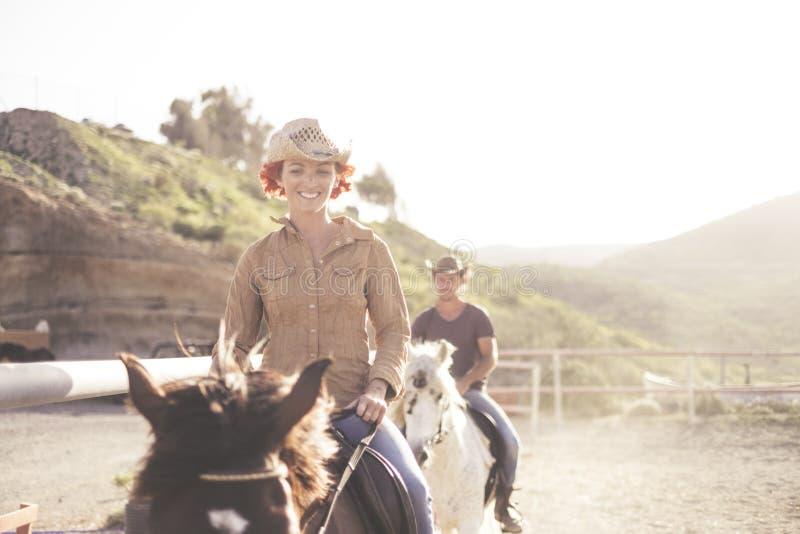 Beaux chevaux de couples d'amis de tour caucasien gentil des jeunes extérieurs dans une école contre-jour du soleil pour l'image  photographie stock