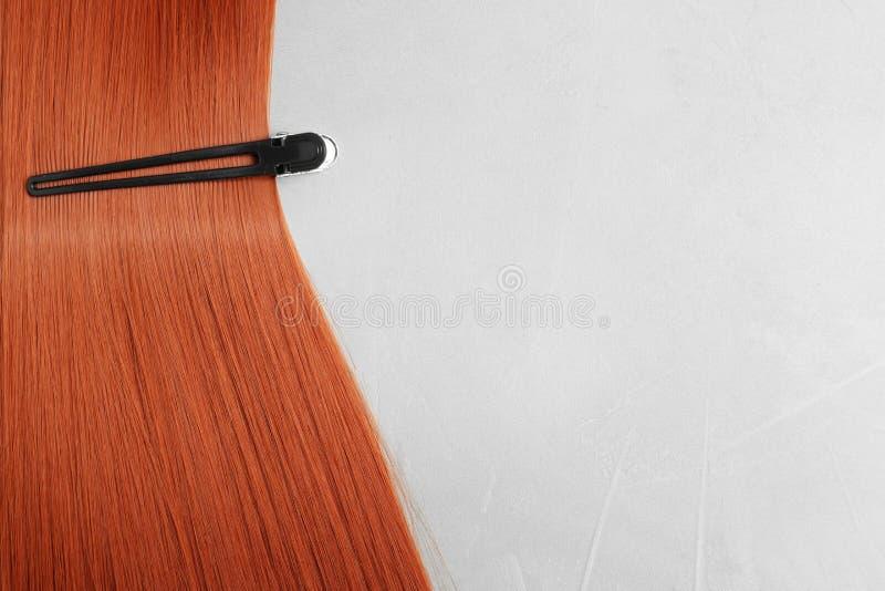 Beaux cheveux et barrette rouges sur le fond clair, l'espace pour le texte images libres de droits