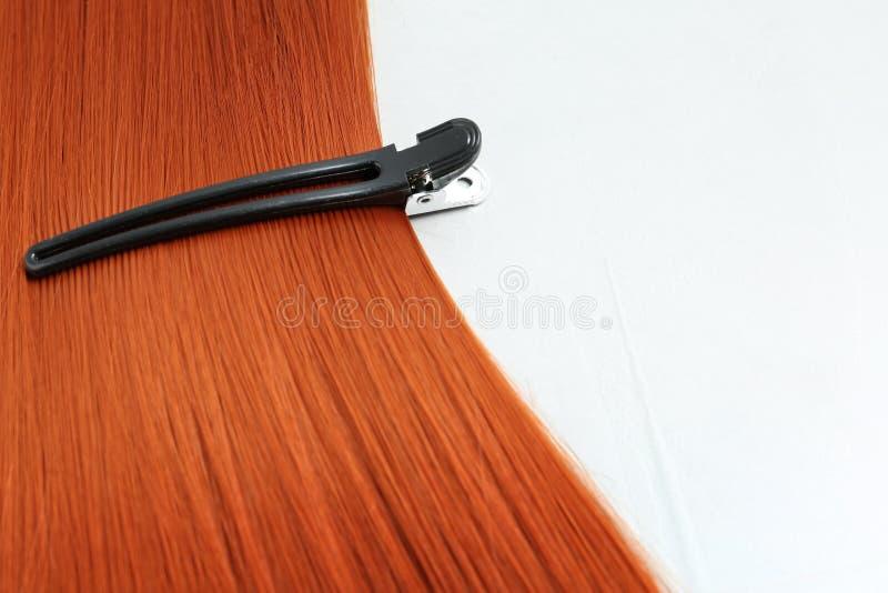Beaux cheveux et barrette rouges sur le fond clair photos stock