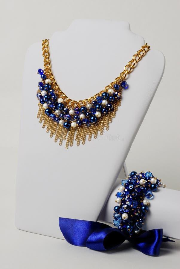 Beaux collier de bleu marine, chaîne d'or et bracelet avec le grand ruban de satin sur un mannequin devant le fond blanc image stock