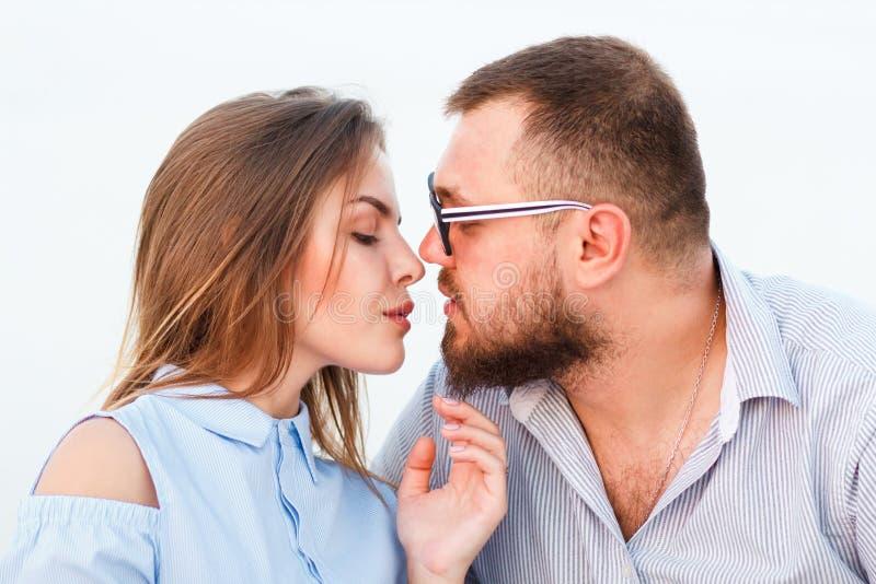 Beaux couples attrayants se reposant ensemble sur la plage blanche de sable, se regardant, jeunes couples embrassant sur la plage image libre de droits