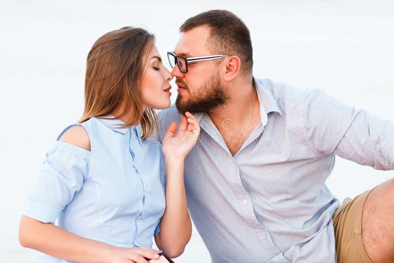 Beaux couples attrayants se reposant ensemble sur le beac blanc de sable images libres de droits