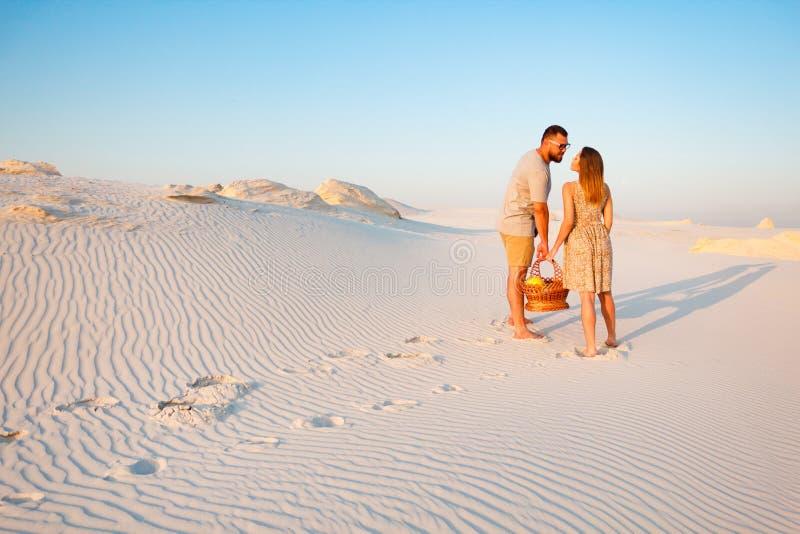 Beaux couples attrayants sur la plage blanche de sable ou dans le désert ou dans les dunes de sable, le type et une fille avec un photo stock