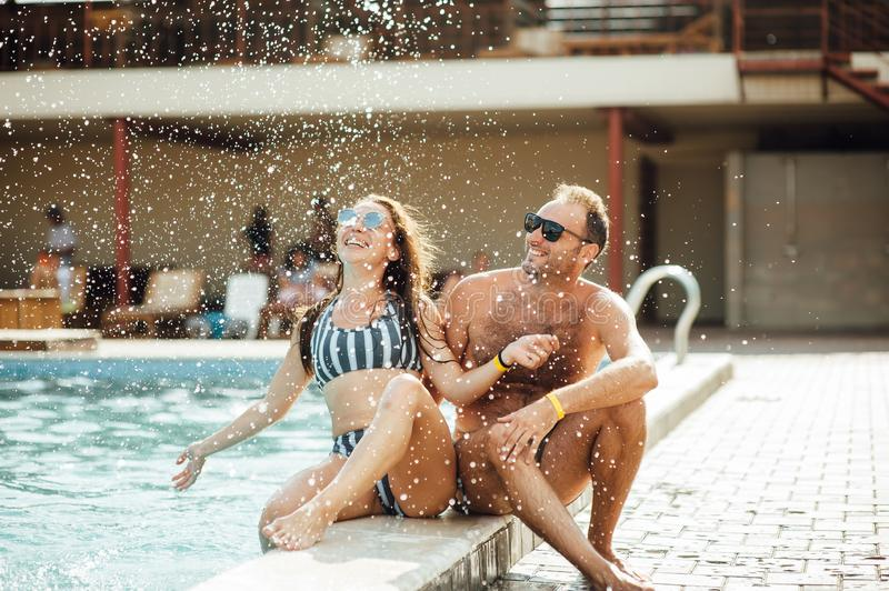 Beaux couples ayant l'amusement par la piscine photo stock