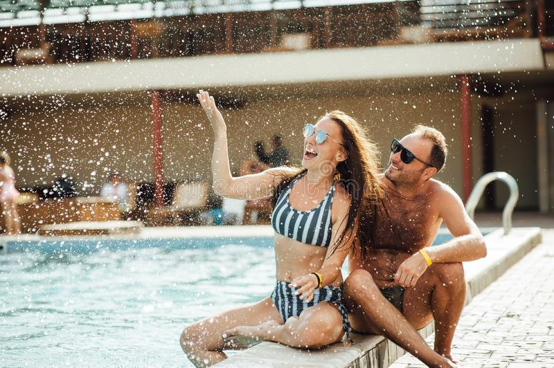 Beaux couples ayant l'amusement par la piscine photos stock