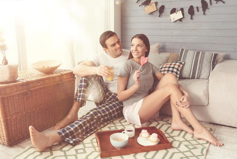 Beaux couples décontractés prenant le petit déjeuner de fête à la maison photos stock