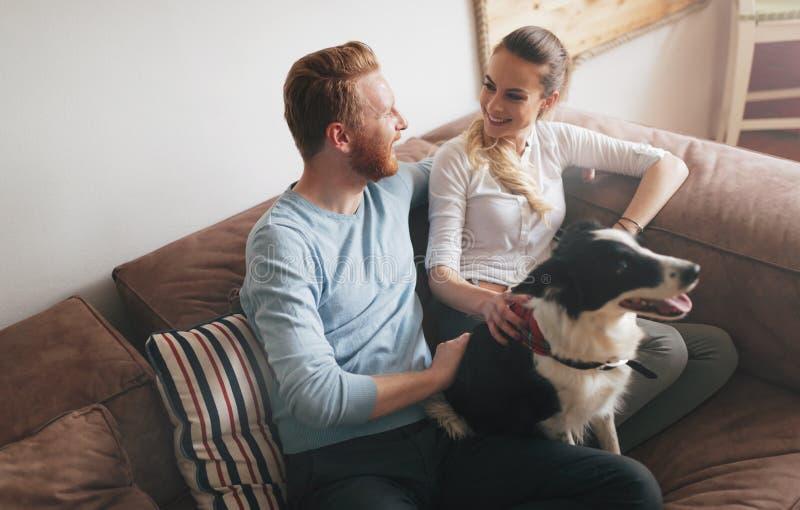 Beaux couples détendant à la maison et aimant leur chien photo libre de droits