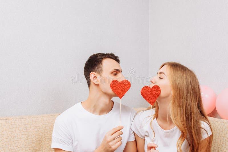 Beaux couples dans l'amour, l'homme et la femme dans le T-shirts blanc, tenant les coeurs de papier, se reposant sur le sofa à la photos libres de droits