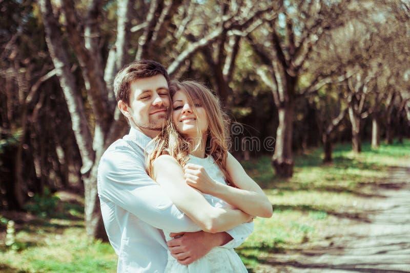 Beaux couples dans l'amour sur une promenade dans la forêt d'été étreignant et regardant à l'appareil-photo image libre de droits