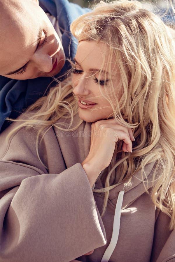 Beaux couples de baiser riants étreignant avec amour et se touchant aux mains sur le fond de centre de la ville closeup photo libre de droits