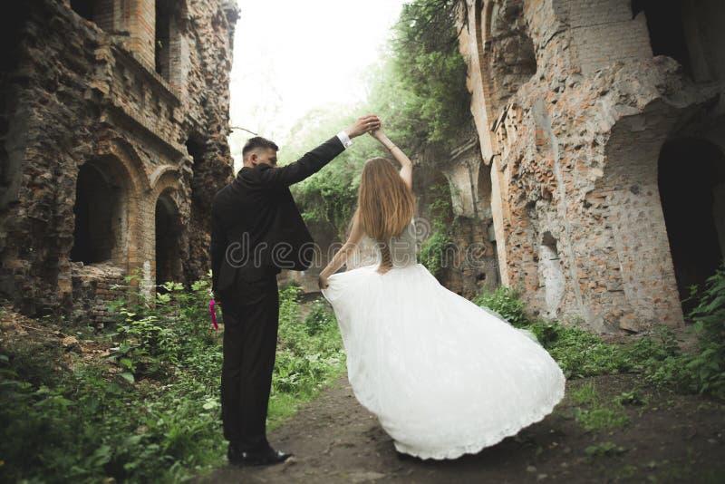 Beaux couples de nouveaux mariés de conte de fées étreignant près du vieux château médiéval image stock