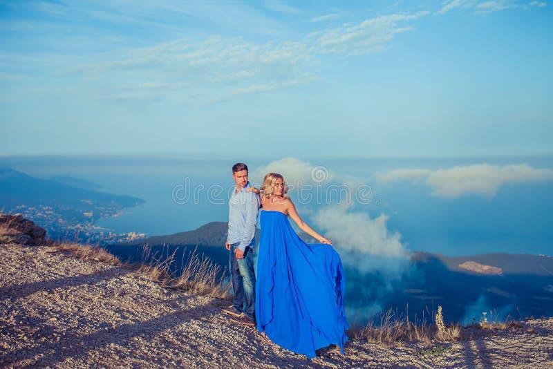 Beaux couples des nouveaux mariés étreignant au jour du mariage sur la falaise avec la vue d'océan Jeune mariée élégante et regar images stock