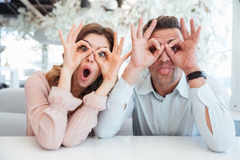 Beaux couples drôles tenant des bras près de leurs visages photo stock