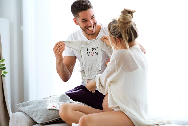 Beaux couples enceintes heureux tenant des vêtements de bébé et souriant sur le sofa à la maison photo libre de droits