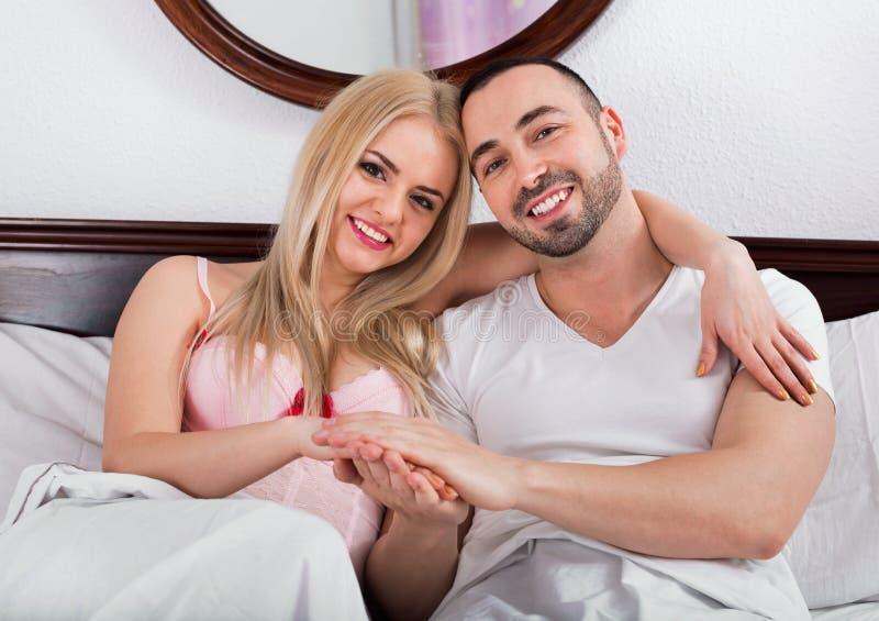 Beaux couples gais posant dans le lit de famille image stock