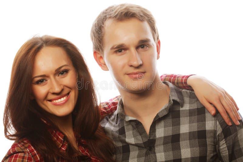 Beaux couples heureux étreignant au-dessus du fond gris images libres de droits