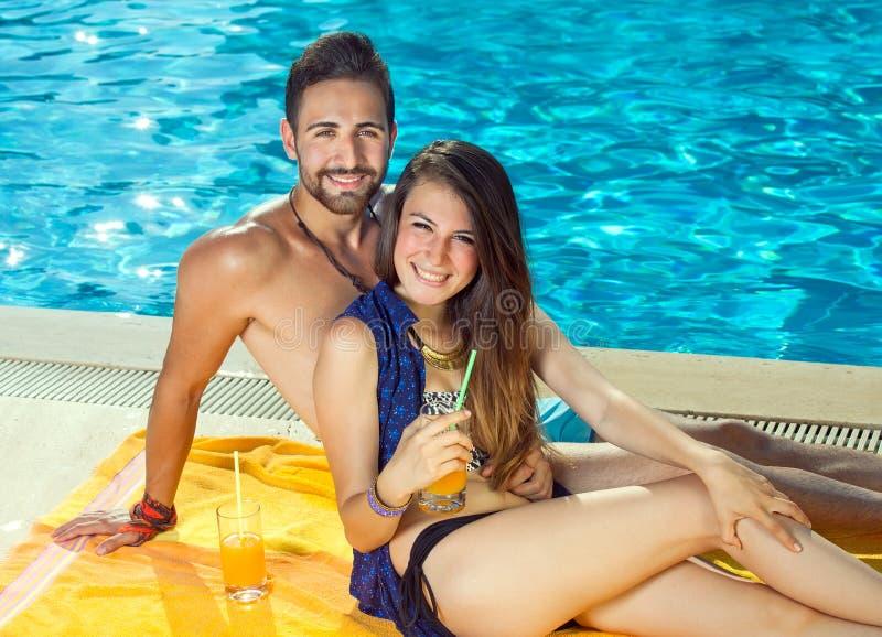 Beaux couples heureux détendant à une piscine images libres de droits