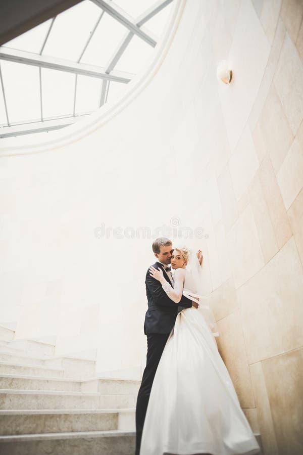 Beaux couples heureux de mariage, jeune mariée avec la longue robe blanche posant dans la belle ville photo stock