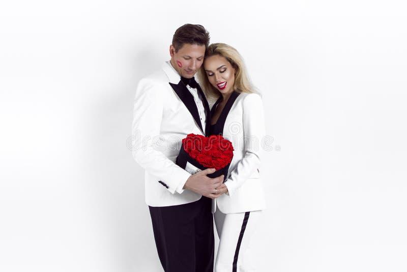 Beaux couples heureux posant sur le fond blanc et tenant la boîte de fleur avec le coeur rouge Jour du ` s de Valentine, épousant photos stock