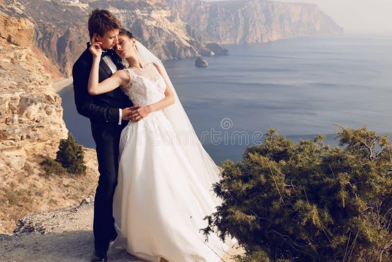 Beaux couples jeune mariée magnifique dans la robe de mariage posant avec le marié élégant sur le coût de mer image stock