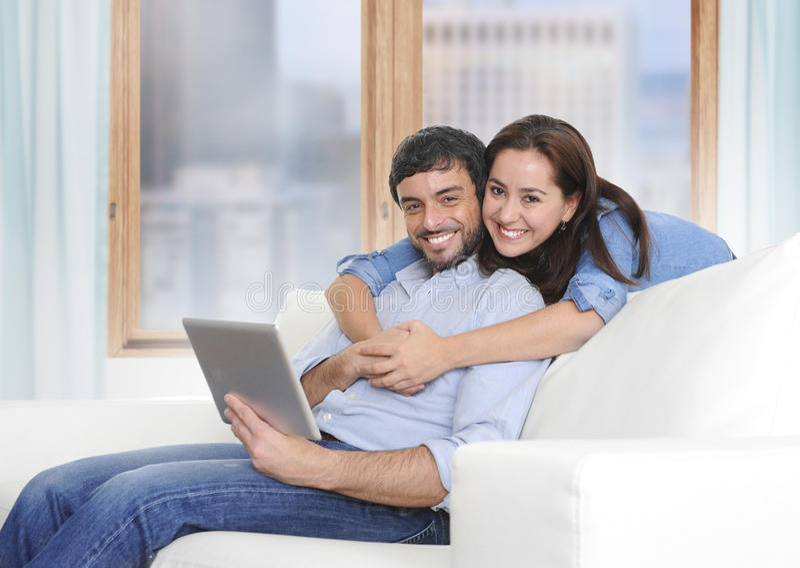 Beaux couples latins dans l'amour se trouvant ensemble sur le divan de sofa de salon appréciant à l'aide du comprimé numérique photo stock