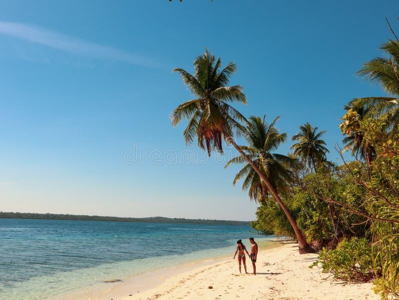 Beaux couples marchant à la plage sablonneuse blanche avec des palmiers en île d'Onok dans Balabac Philippines images libres de droits