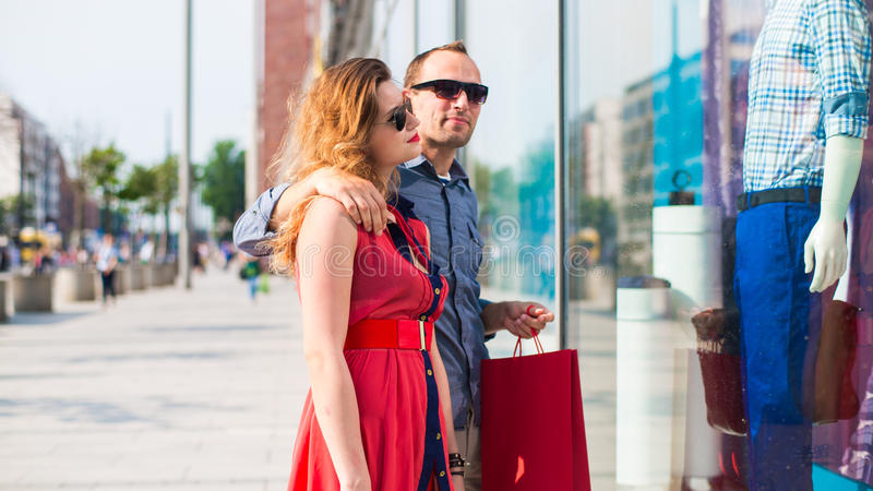 Beaux couples marchant par le mail portant beaucoup de paniers. photo libre de droits