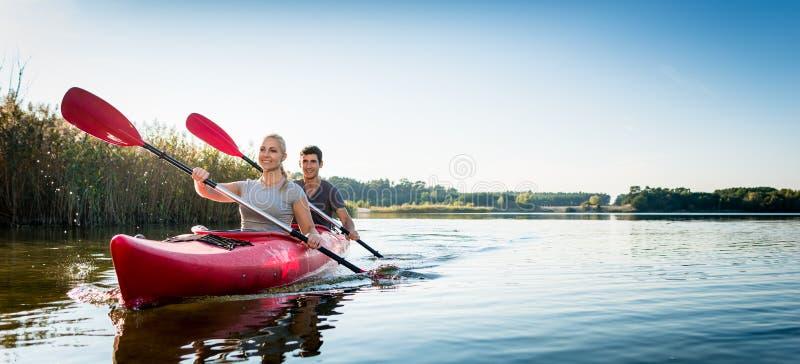 Beaux couples naviguant le kayak sur le lac image stock