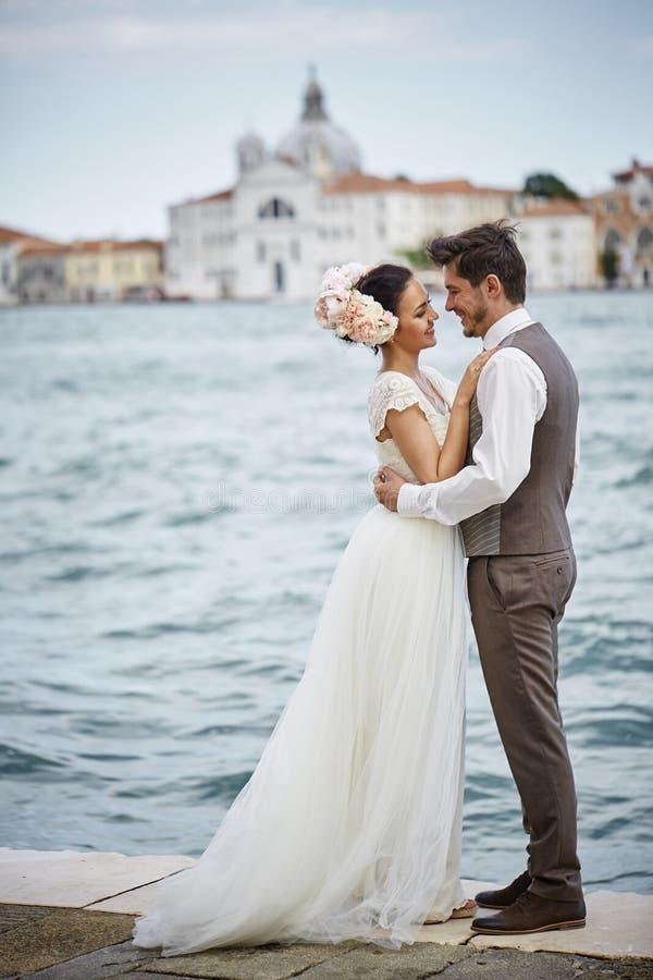 Beaux couples nuptiales au coucher du soleil sur les rues de Venise image stock
