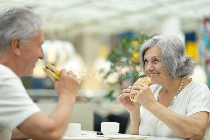 Beaux couples pluss âgé mangeant des aliments de préparation rapide images libres de droits