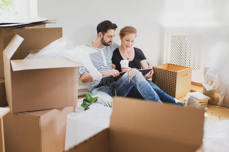 Beaux couples regardant l'album photos tout en déballant la substance après la relocalisation à la nouvelle maison images stock