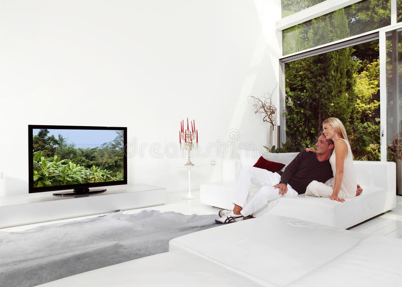 Beaux couples regardant la TV photos stock