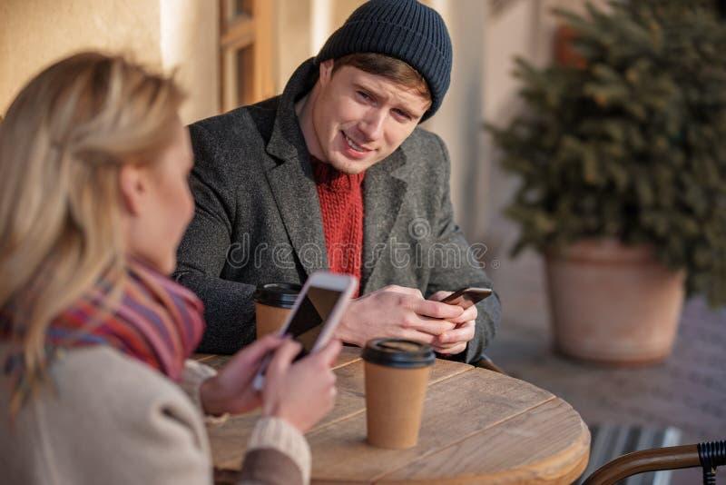 Beaux couples se reposant au café avec des mobiles photographie stock