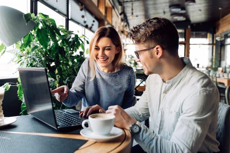 Beaux couples se reposant au café avec l'ordinateur portable image stock