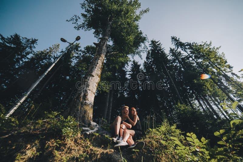 Download Beaux Couples Se Reposant Dans Une Forêt Près De L'arbre Photo stock - Image du joie, occasionnel: 76077666