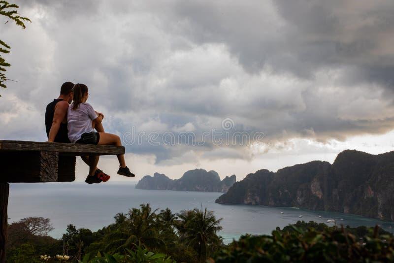 Beaux couples se reposant sur la plate-forme en bois avec les vues d'île de Phi Phi et le ciel nuageux image stock
