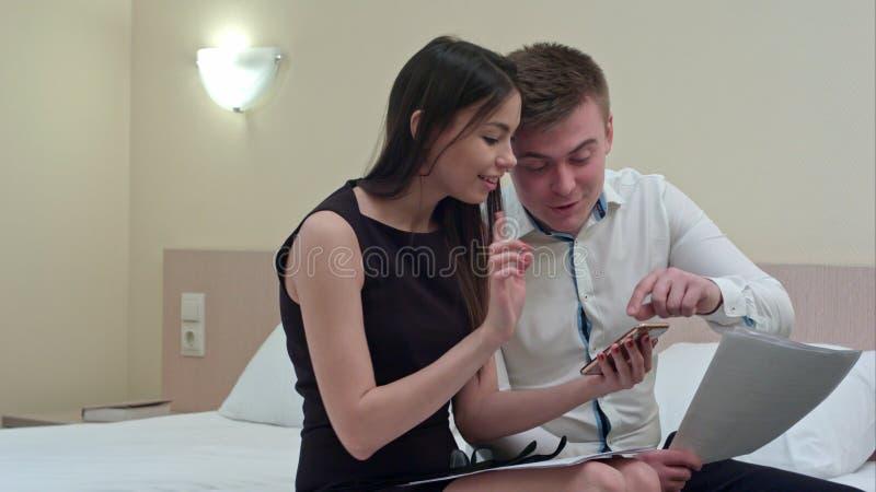 Beaux couples se reposant sur le lit et à l'aide du smartphone, semblant heureux ensemble image stock
